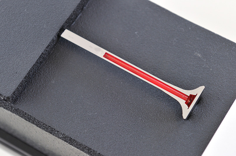 ナトリウム封入バルブのカット見本。赤く塗られた部分が封入エリアで、軸部分だけでなく傘部分にまで熱伝導率の高いナトリウムを封入し、エンジン内部の放熱性を高める