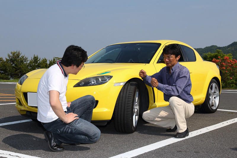 駐車したRX-8の前で、岡本氏から運転操作とタイヤの関係性をレクチャーされている筆者