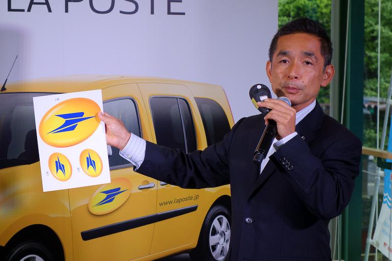 カングー ラ・ポストの概要を紹介した広報グループの近棟伸弘氏。近棟氏が持つステッカーが、購入者にプレゼントされるもの