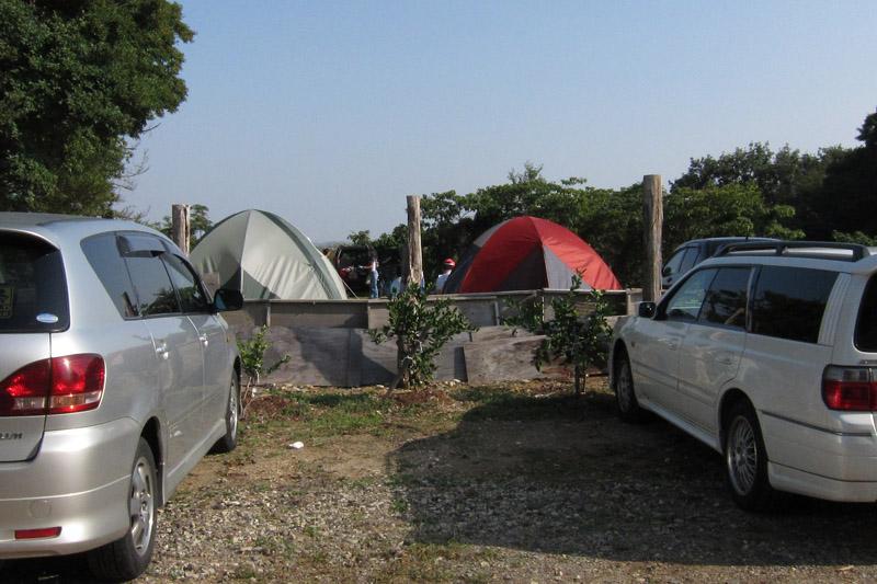 民間駐車場内にテントを張って宿泊する人