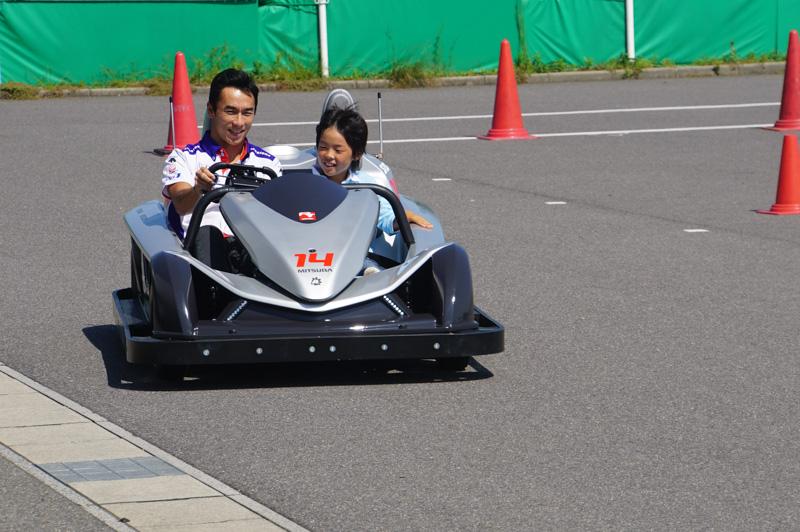 モデルの男の子を乗せて走る佐藤琢磨選手