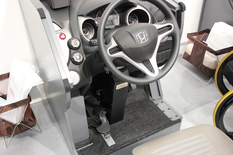 片足でステアリング操作ができる足動運転補助装置「フランツシステム」も展示。新型フィット向けはまだ開発中だが、ホンダ車では過去に100台ほどが装着しているという