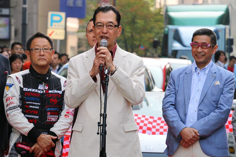 自工会 会長の池史彦氏。東京モーターショーの60周年を人間の還暦にたとえ、参加者全員が「赤いなにか」を身につけていると紹介。自身はチェック柄の赤いシャツを着用しているほか、運転中は赤いドライビンググローブを使っていた。右側後方に立っている日産自動車の 西川廣人代表取締役副社長は、キャラクターも使われたかわいらしい眼鏡を着用している