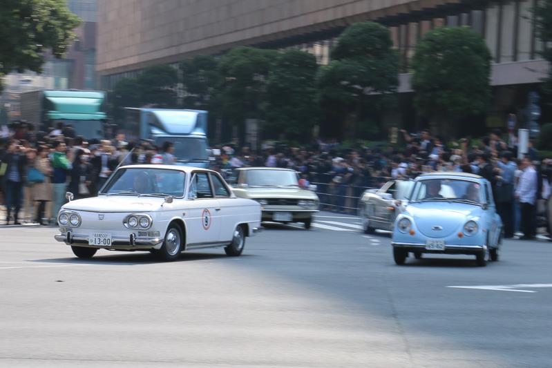 左側の「コンテッサ 1300 クーペ」を運転するのは日野自動車 代表取締役社長の市橋保彦氏。右側の「スバル 360」を運転するのは富士重工業 代表取締役社長の吉永泰之氏