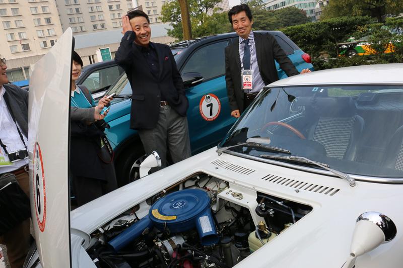 駐車スペースに止めた「コスモスポーツ」の前で報道陣からの取材に応じるマツダ 代表取締役社長兼CEOの小飼雅道氏(中央)。東京モーターショー2015ではできるだけ多くの人にブースに足を運んでもらい、実車を見学してほしいと語る。ロータリーエンジンについては開発を続けていることを認めつつ、具体的な施策については明言を避けた