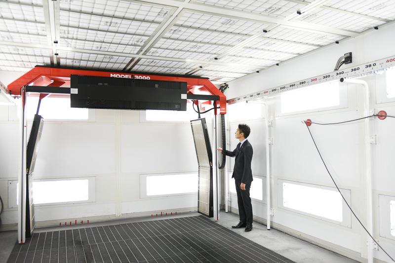 ネッツトヨタ富山本店に導入されたスリーエムジャパンの自動車用塗装乾燥装置「3M クイックドライシステム」。見上げているのは、ネッツトヨタ富山株式会社 代表取締役社長 笹山泰治氏