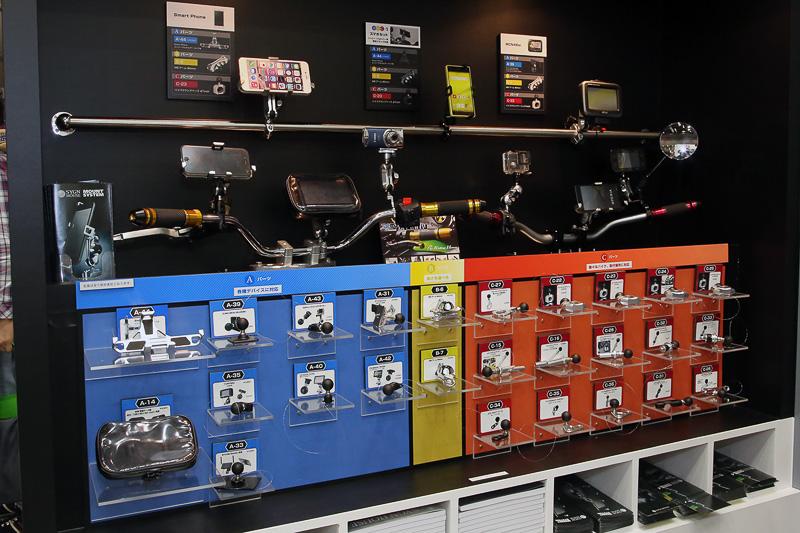 SYGN HOUSEブースではスマホなどをオートバイに固定するマウントシステムを多数展示