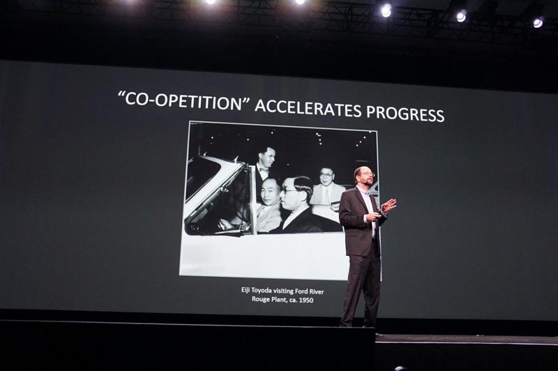 豊田英二氏がまだトヨタの取締役だったころにフォードの工場を訪れた古事を紹介し、自動車業界は競争しながら協力していると指摘した