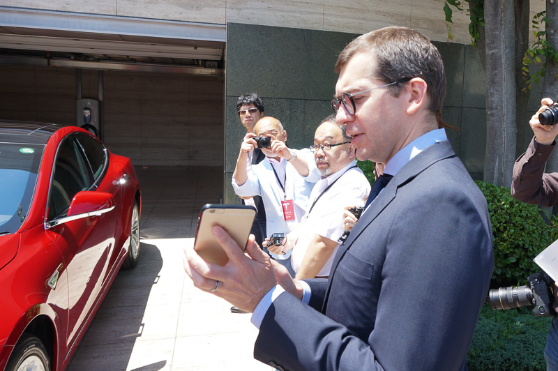 スマートフォンの画面を示しながら新機能「サモン」について解説するテスラモーターズ ジャパン 代表取締役社長 ニコラ・ヴィレジェ氏