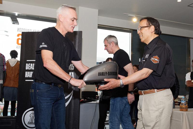 ハーレーダビッドソン三鷹の代表である大坪政俊氏に、記念トロフィーとしてロードスターのタンクが授与された
