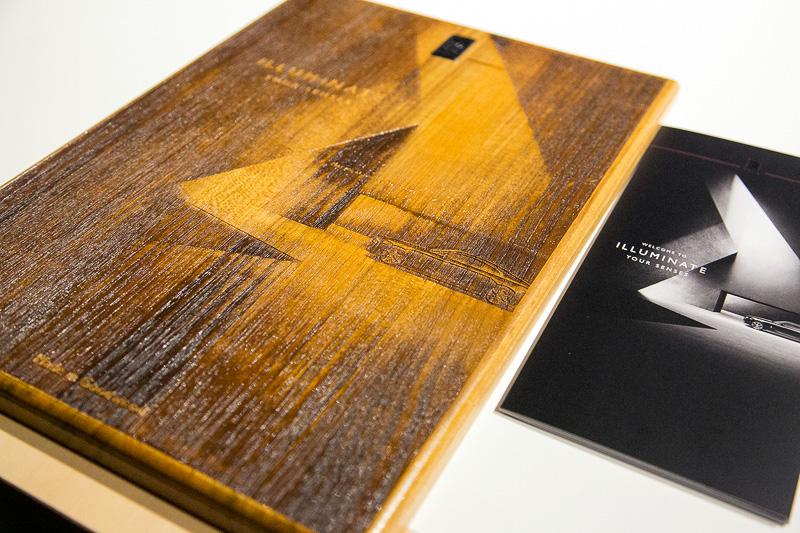 オーダー製作した寄せ木細工を盛り込んだパネルの例。中央の作品はパネル作りに使っているレーザーカットの技術を使ったオブジェ。レーザーの照射温度を変えて模様を描いている。ベースになっている図柄は今回の展示会のパンフレット写真