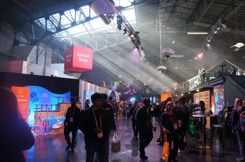 GitHub Universe 2018会場。各社の展示ブースや、GitHubノベルティーの販売コーナー、各種企画などが並ぶ奥に講演会場がある