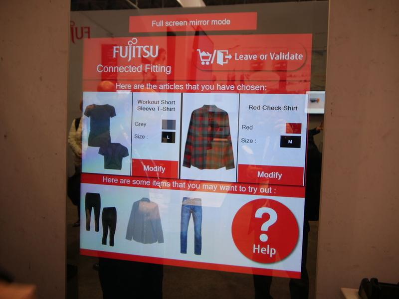 富士通のスマートフィッティングルーム。試着してサイズが合わなかった場合などにはデバイスを通じて伝えると、店員が持つスマートウオッチなどに情報が伝わり、持ってきてくれる