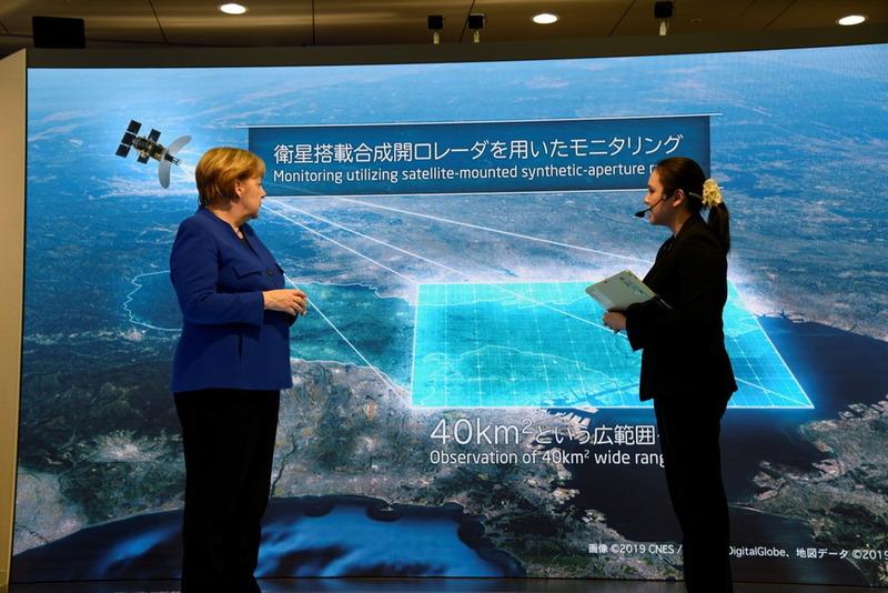 人工衛星による都市インフラモニタリングソリューションの説明を受けるメルケル首相