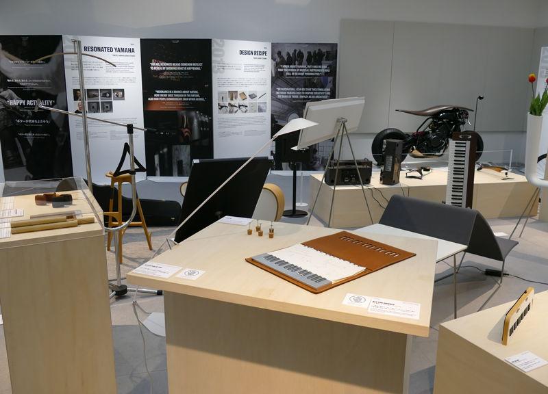 「未来をカタチに -ヤマハデザインの流儀-」の展示の一部。後ろにちょっとだけみえるバイクは、お互いにデザインアイテムを交換してみようというヤマハ発動機との共同実験でヤマハによるデザイン。楽器のデザイナーがバイクをデザインしたら?という面白い取り組みだ