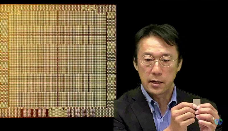 Power10の実物を手に持った日本IBMの間々田隆介氏(テクノロジー事業本部 IBM Power事業部 製品統括部長)。サイズは切手より少し大きい600平方ミリメートル。背景は拡大写真