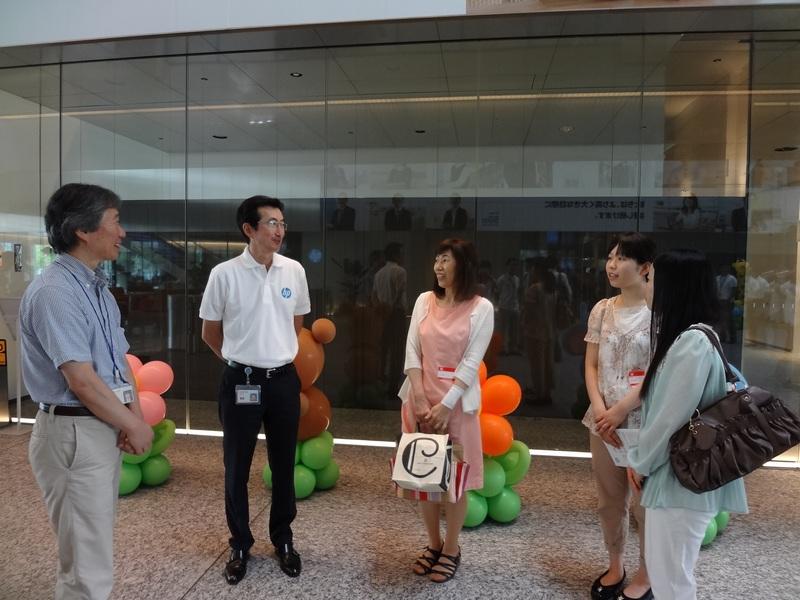 社員の家族を出迎える小出社長(左から2人目)