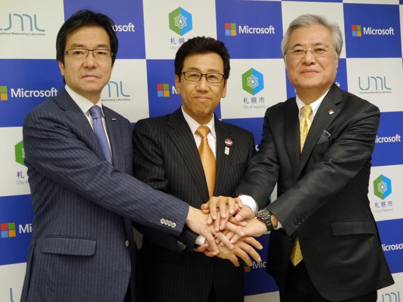 1月20日に開催された、札幌市、YRPユビキタス・ネットワーキング研究所(YRP UNL)との共同記者会見に出席した樋口会長(左)。真ん中が札幌市の秋元克広市長、右がYRP UNLの坂村健所長