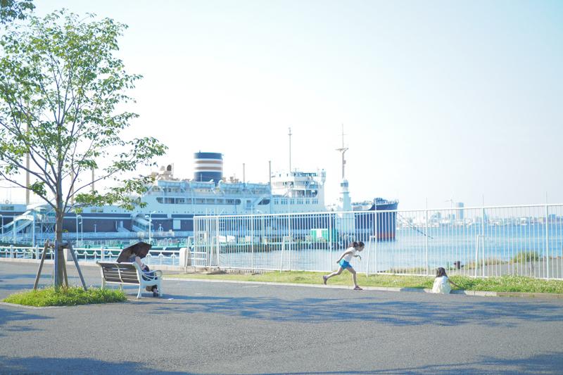 """なんと穏やかな昼下がりの風景なのだ! とうれしくなってシャッターを切った。傾きかけた光と港の風景を爽やかに、駆け出す子どものきらめきを大切にした。<br><span class=""""fnt-85"""">オリンパス PEN-F / M.ZUIKO DIGITAL 25mm F1.8 / 25mm(50mm相当) / 絞り優先AE(F1.8、1/2,000秒、+2.0EV) / ISO 200</span>"""