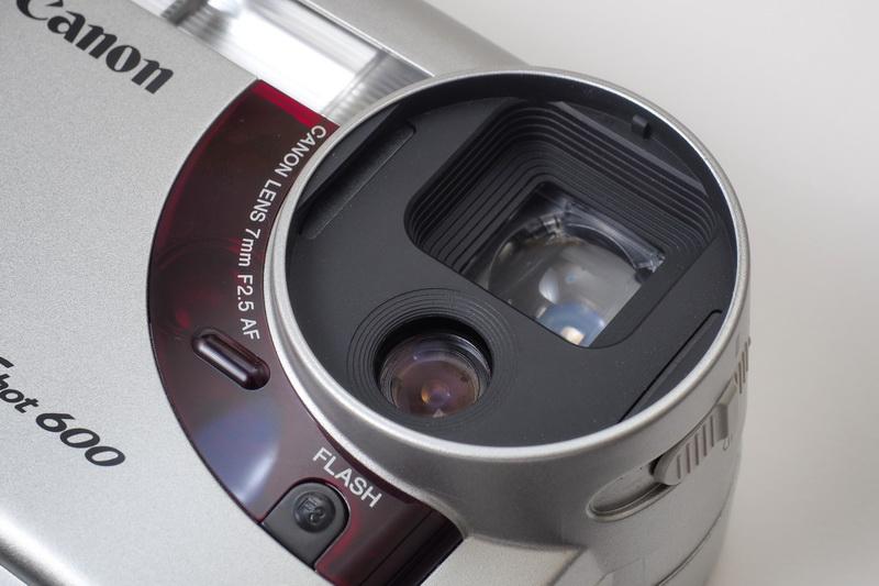 PowerShot 600の搭載レンズ。ちなみに丸枠の中の下側がレンズで上は光学ファインダー。単焦点と言われるとグッとくるものがあるけど……