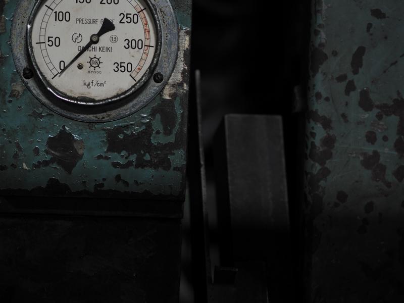 """作業場の片隅にある機械に、微かな光が届いていた。塗装の剥げや、擦り傷、へこみ。みな時間が作り上げてきた独特の形だ。<br><span class=""""fnt-85"""">オリンパス PEN-F / M.ZUIKO DIGITAL ED 75mm F1.8 / 75mm(150mm相当) / マニュアル露出(F2、1/60秒) / ISO 400 / WB:5,300K</span>"""