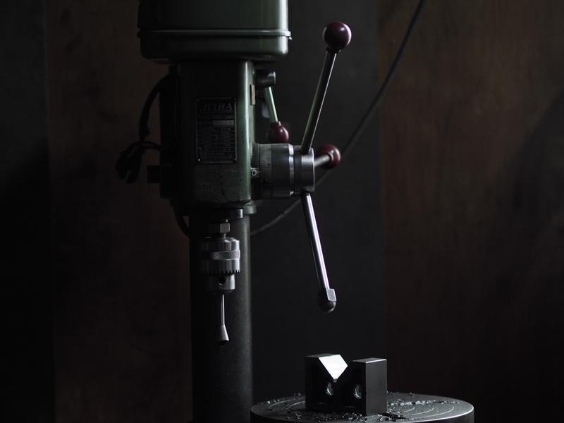 """私は工具を扱えないし、工作機械の使い方も分からない。作業場を見つめていると、遠い世界が目の前にあるように思えてくる。<br><span class=""""fnt-85"""">オリンパス PEN-F / M.ZUIKO DIGITAL ED 75mm F1.8 / 75mm(150mm相当) / マニュアル露出(F2、1/60秒) / ISO 400 / WB:オート</span>"""