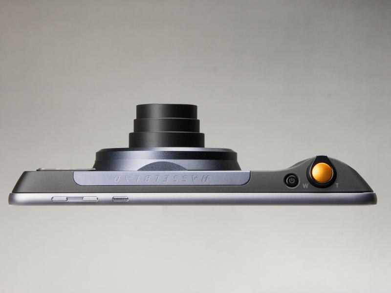 本体上部。ズームレバー一体型のシャッターボタンはオレンジ色のアクセントになっている。ズームレンズは沈胴式だ