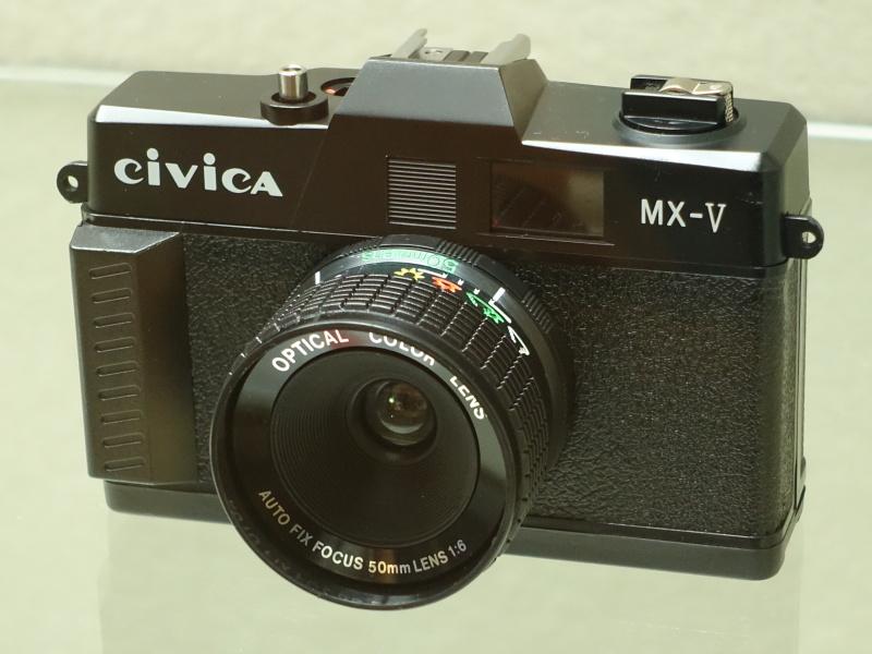 台湾の「シヴィカMX-V」(メーカー不明、1980年代半ば)。台湾ではトイカメラが盛んに作られた時期があり、その中でも比較的しっかりつくられたものだという。天気マークに合わせて絞りを操作するだけの固定焦点レンズと見られるが、銘板に「AUTO FIX FOCUS」とあるのが面白い。