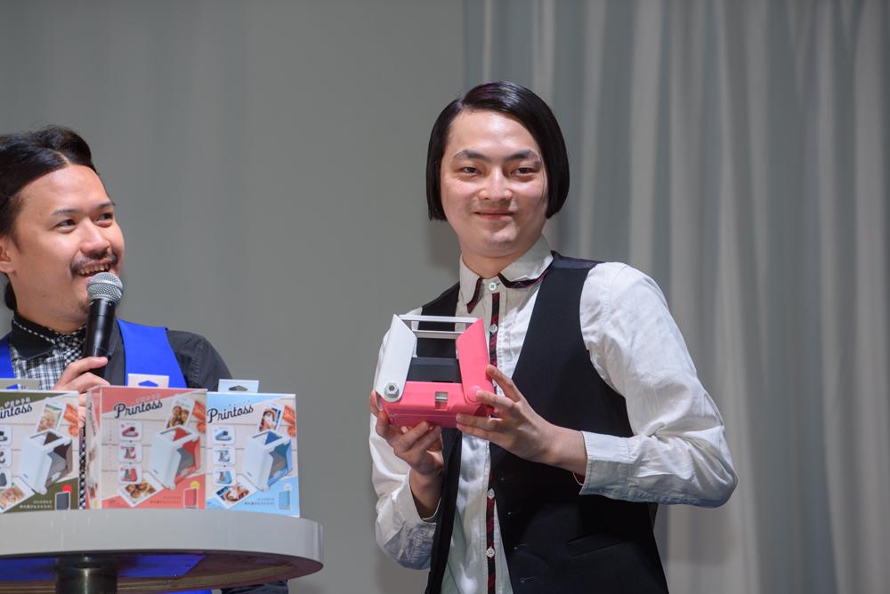 筧さんが気に入ったという「SAKURA」カラーのプリントスを手に、すましたポーズで笑いをとるピスタチオの小澤慎一朗さん。