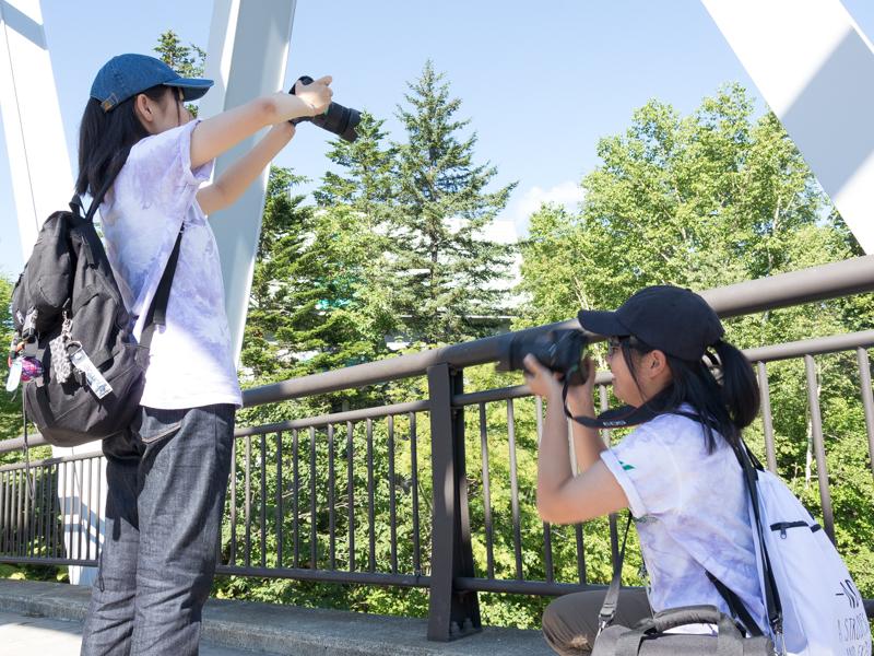 白ひげの滝近くの橋の上で撮影する選手