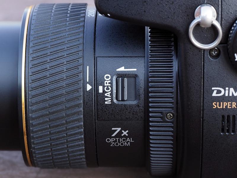 レンズ鏡筒の側面に配置される「マクロ切り替えレバー」。マクロに切り替えると、望遠側だと多少ズームできる。だが、広角側は広角端に固定される。