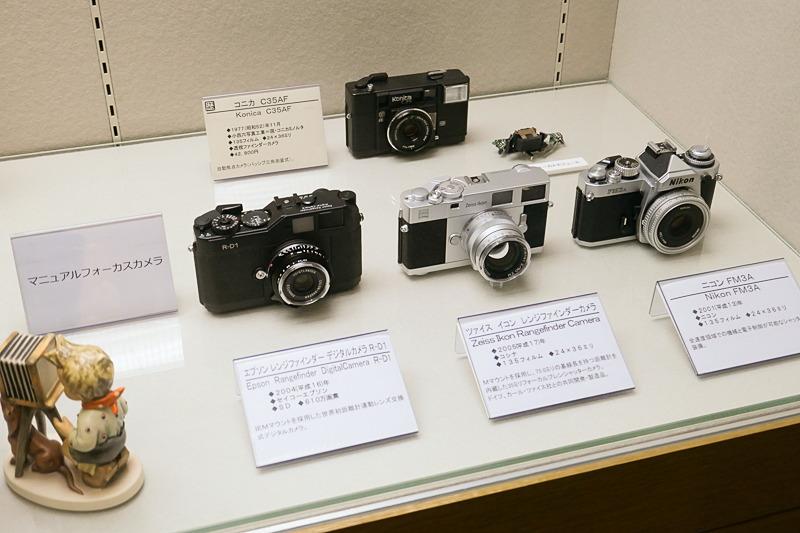 """「ピントの魔法」より、様々なマニュアルフォーカスカメラ。一番後ろは、オートフォーカスを広めた歴史的カメラ""""ジャスピンコニカ""""。"""