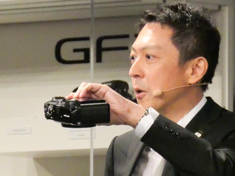 GFX 50Rを手に、ボディの薄さを示す。