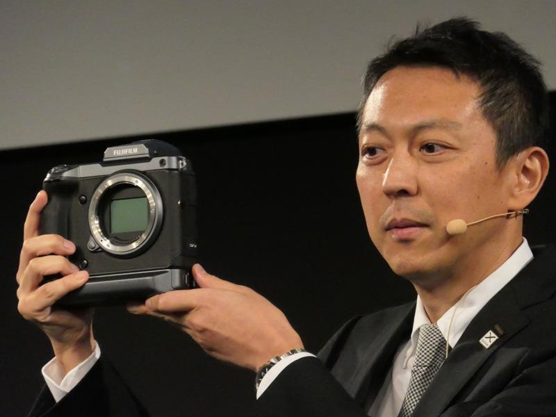 開発発表の「GFX 100 MEGAPIXELS」を手にする飯田年久氏。