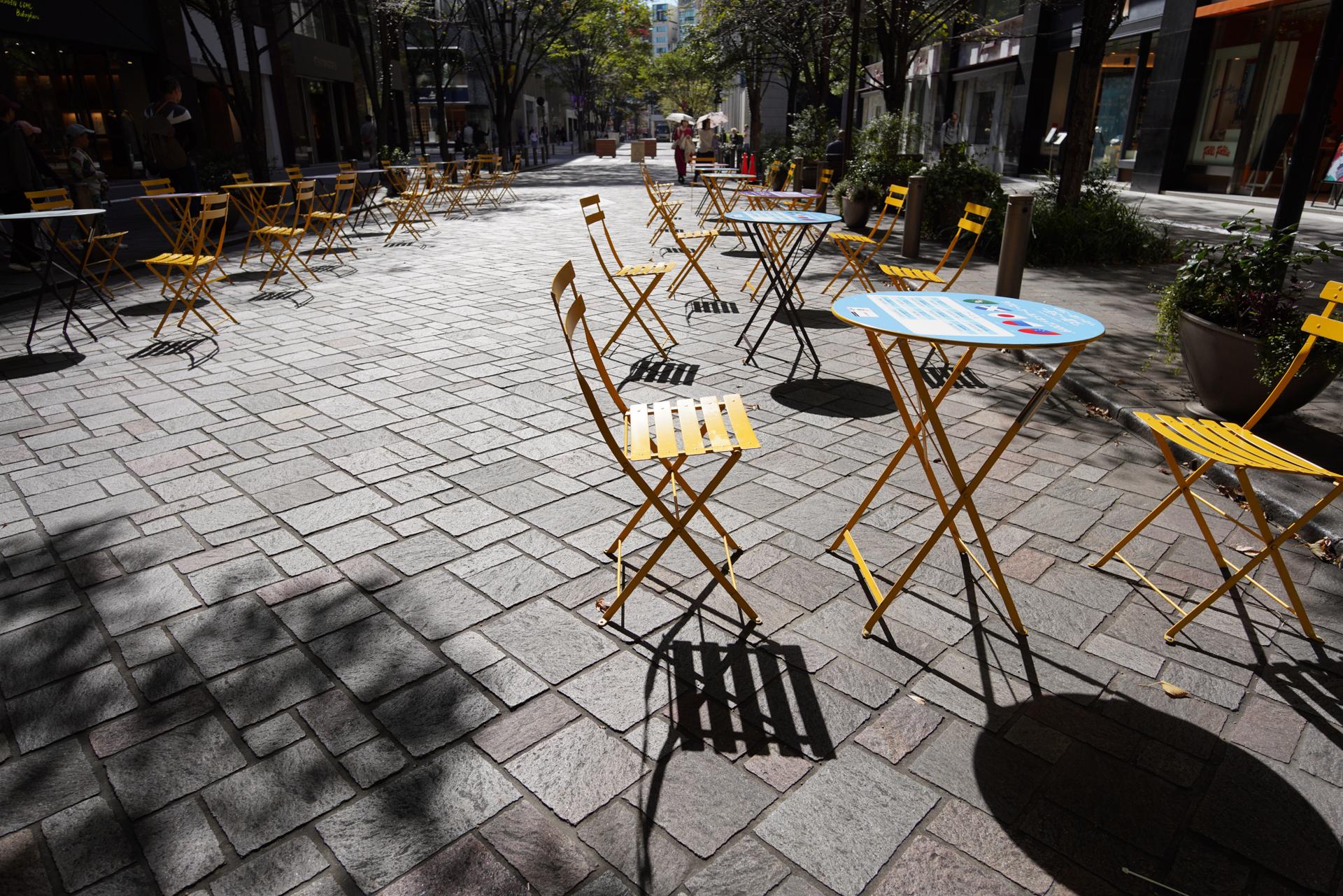 丸の内通りは、平日と休日で時間帯は違うが365日間歩行者天国になる。テーブルが置かれて街角カフェのようになった雰囲気を狙った。陰影を強調するために逆光で、広さを加えるために腰ぐらいの高さから撮影した。α7R III / ISO 100 / F5.6 /  1/500秒