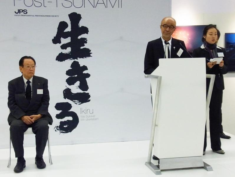 「生きる」写真展にて挨拶を述べる実行委員長の菅洋志氏と日本写真家協会会長の田沼武能氏(いずれも当時)、2012年フォトキナ会場にて。市川さん提供