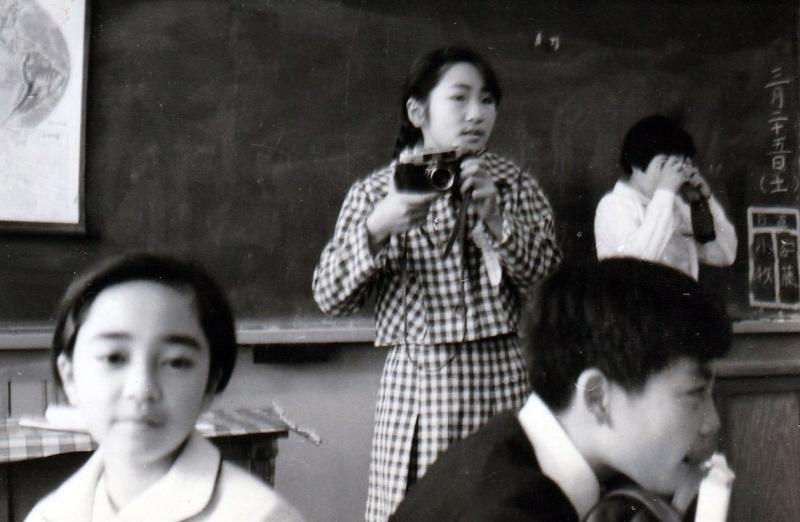 小学生の頃に教室でカメラを構える千代田さん