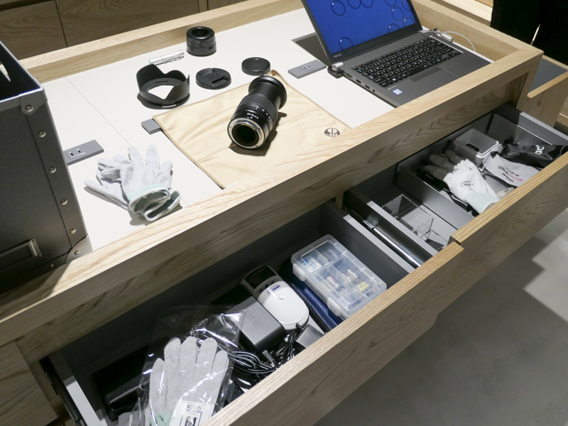 作業台の一部。バッテリーチャージャーを並べることを考えて、コンセントは間隔を空けて複数設置。預かり品はひとつの通い箱にまとめて扱う。