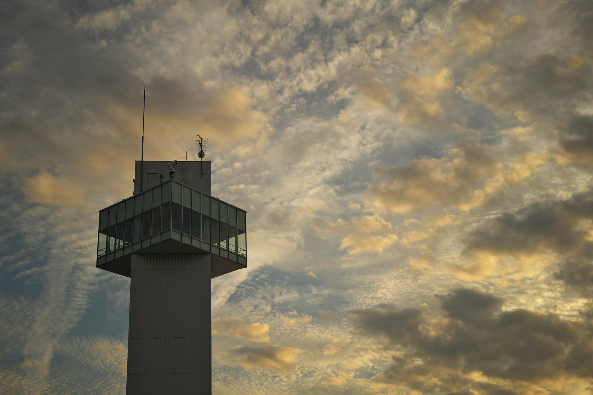 逆光での管制塔。空の雲の再現が美しくてシャッターを押す。絞り開放だが、周辺光量が落ちない。また階調のつながりがいい。<br>α7R IV APO-LANTHAR 50mm F2 Aspherical E-mount(F2・1/6,400秒)ISO 100