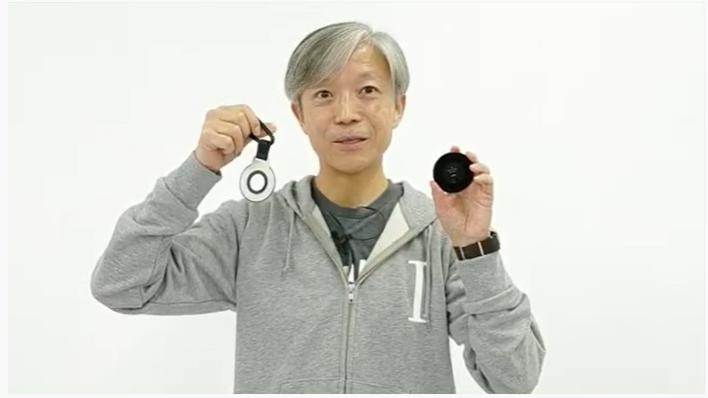 マグネット式メタルキャップとレンズキャップホルダーを持つ山木氏。