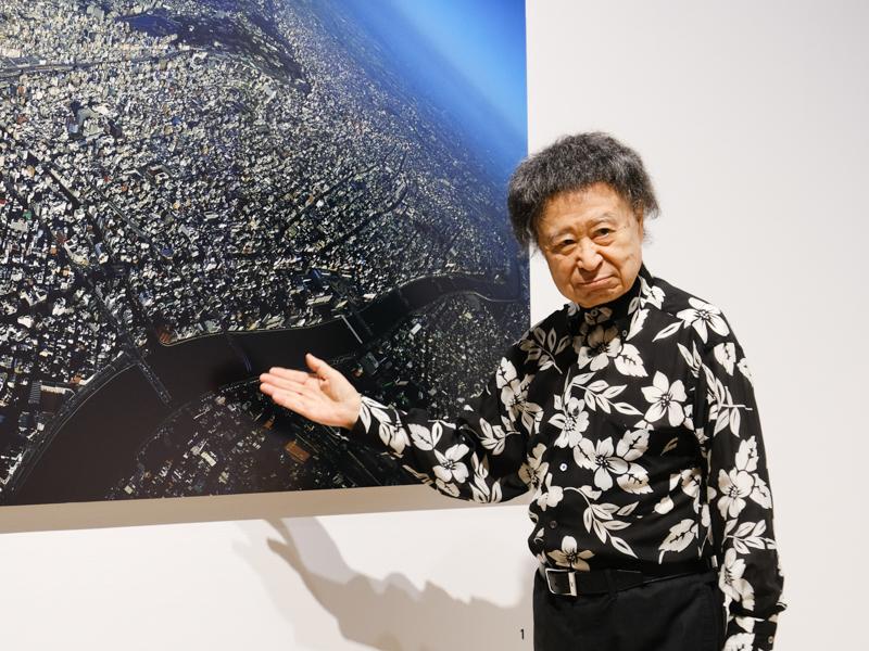 """篠山紀信氏。独自の手法""""シノラマ""""で撮影した作品「TOKYO NUDE 1986-92」の前で"""