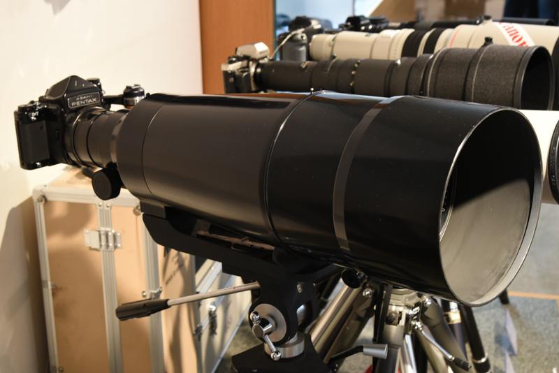 """とりわけ大きなレンズは「Super-Multi-Coated TAKUMAR / 6×7 1:4/800」(製造年不詳。旭光学工業:現リコーイメージング)<span class=""""fnt-85"""">※6月22日17時修正:製品名に誤りがあったため、日本カメラ博物館に確認のうえ修正しました。</span>"""