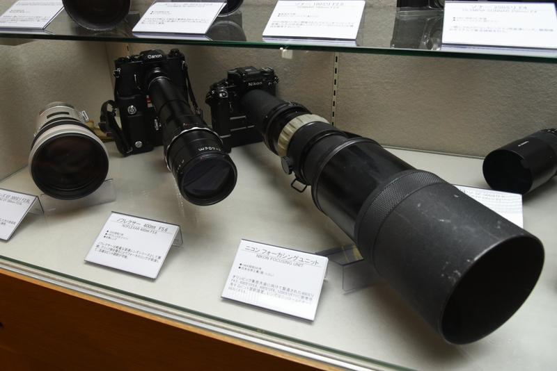 ニコンフォーカシングユニット(右。1964年。日本光学工業:現ニコン)。オリンピック東京大会に向けて製造された400mm F4.5、600mm F5.6、800mm F8、1200mm F11に装着して使用するピント調節装置。写真はニッコールPオート600mm F5.6