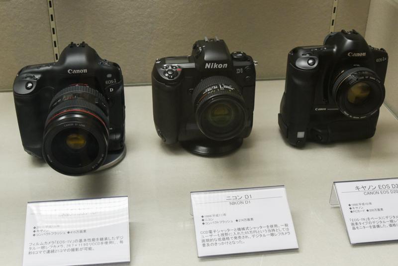 中央のニコン D1(1999年。ニコン)はCCD電子シャッターと機械式シャッターを併用し、一般ユーザー向も視野に入れて発売されたモデル。同カメラの登場以降、デジタルカメラが報道の分野でも多く使用されるようになり、撮影から公開までの時間が大幅に短縮されるようになったという