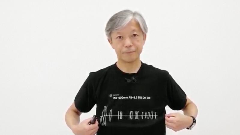レンズ構成図Tシャツを身につけた山木和人氏(株式会社シグマ代表取締役社長)。「新製品プレゼンテーション 8月4日」(YouTube)より