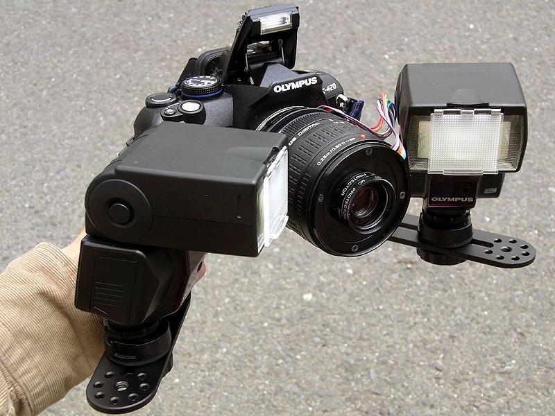 <b>自作改造したリバースマクロ14-42mmをE-420に、「マクロフラッシュブラケット」と「エレクトロフラッシュFL-36」2台を装着してみた。レンズ前約4cmの被写体を照明するため、発光部が内向きになっている。FL-36はE-420とワイヤレスで同調し、TTL調光や、2台それぞれの調光補正なども行なえる</b>