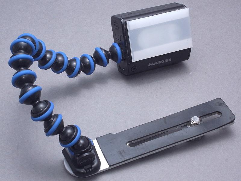 <b>以上の3点を切り貼り(ブリコラージュ)すると、「クネクネ曲がるスレーブストロボブラケット」になる。ゴリラポッドの脚のジョイントはグッと引っ張ると「キュポ!」と外れ、連結して延長することもでき、その特徴を利用している。このジョイントの先端は、スレーブフラッシュのボディにネジ止めされている。乳白色アクリル板のディフューザーは、マジックテープで発光部に止めている。ストロボブラケットのゴムも、自分の好みで薄手のものに張り替えている</b>