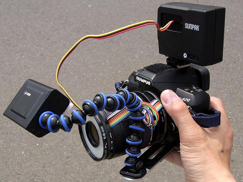 <b>逆光用スレーブストロボをカメラに装着するとこんな感じ。レンズのワーキングディスタンスは約4cmなので、ストロボはだいたいこんな位置にセットされる。高倍率マクロシステムとしては非常ににコンパクトで、手持ち撮影も楽に行なえる(と言っても基本的に大変な撮影なのだが)。しかし配線だらけの外見はいかにも怪しげで目立つ</b>