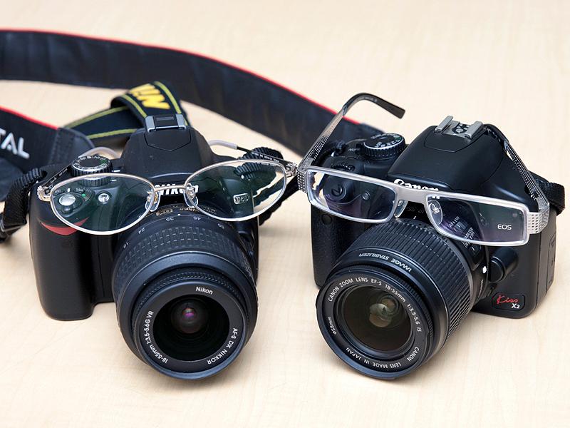 <STRONG>さくら氏愛用のD60(左)と杜氏愛用のEOS Kiss X2(右)。お2人のメガネとともに</STRONG>