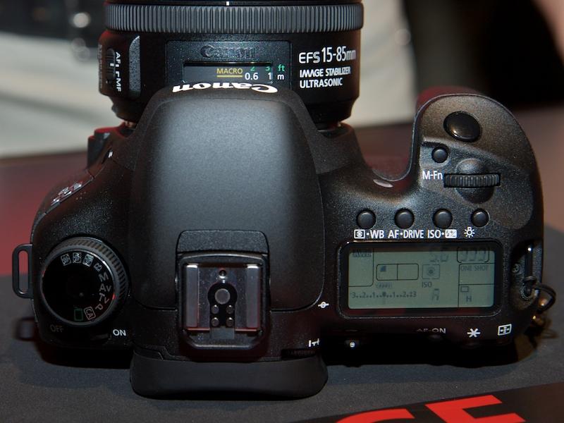 <b>上面。モードダイヤルはEOS 50Dのシルバーと異なり黒色。メイン電子ダイヤル脇のM-Fnボタンも新機能</b>